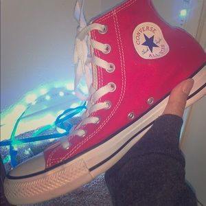 A pair of red chuck taylor's high top converse